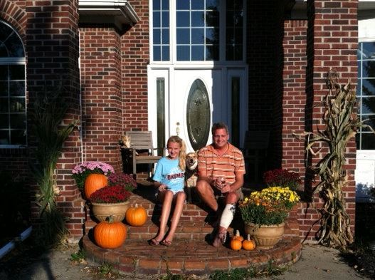 This was taken in fall 2011. My porch decor has improved since then, but I like this picture because of the dog squeezing her head between the two of them.